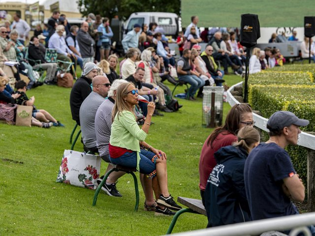 Visitors to the first day of the show relax in the fine weather to watch the showjumping in the main ring. . Picture Tony Johnson