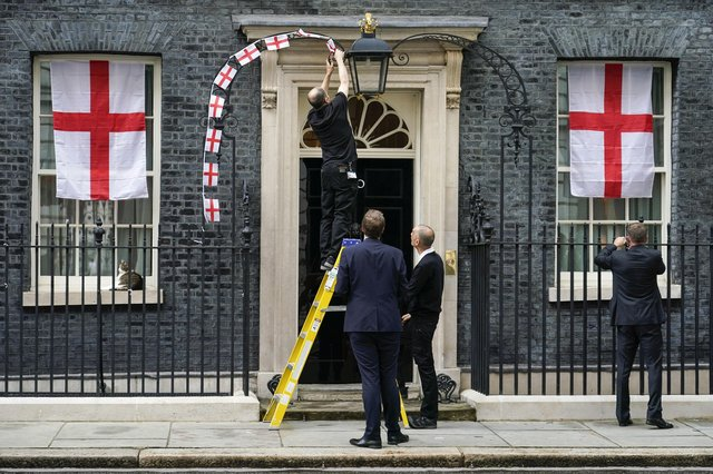 England flag bunting decorations are removed from outside 10 Downing Street after Italy beat England to win Euro 2020