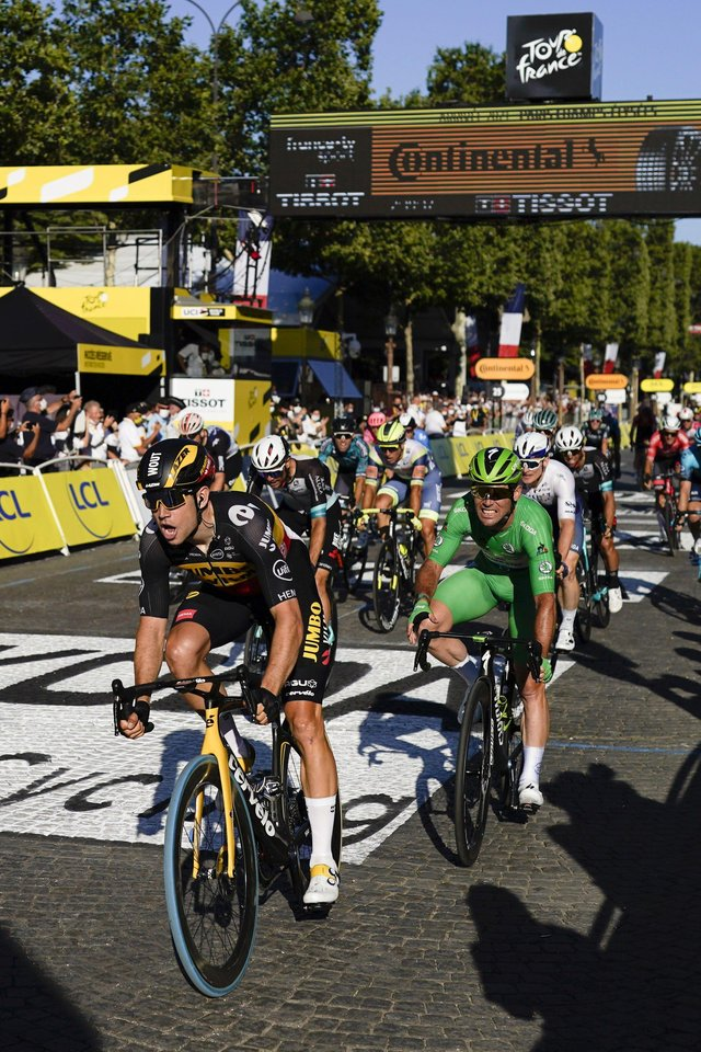Belgium's Wout Van Aert crosses the finish line to win ahead of Britain's Mark Cavendish, wearing the best sprinter's green jersey, right, on the Champs Elysees in Paris. Picture: AP/Daniel Cole.