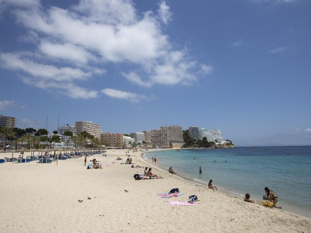 Tourists sunbathe at Magaluf Beach in Calvia, on the Balearic Island of Mallorca. British holidaymakers heading to the Balearic Islands will need to show a negative PCR test or proof of vaccination due to a rise in UK Covid infections, Spain said, reversing a free-entry policy. (Photo by JAIME REINA/AFP via Getty Images)