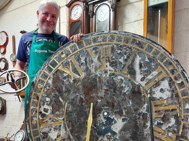 Horologist Andrew Bates with the clock