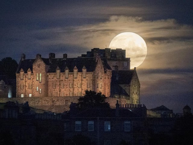 A full moon rises behind Edinburgh Castle on July 23, 2021