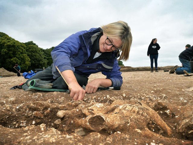 Volunteer Lucy Crosbie cleaning one of the many cow skulls placed round the shrine Picture: Jonathan Gawthorpe