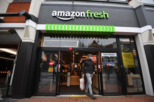 Customers scan a smartphone app when entering Amazon Fresh (PA Media)