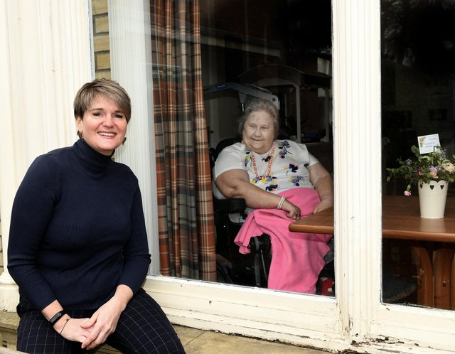 Elizabeth Hancock (L), Manager of Fulford Nursing Home with resident Julia behind the window .
