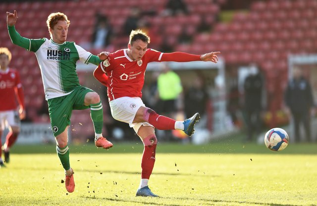 BARNSLEY, ENGLAND - FEBRUARY 27: Cauley Woodrow of Barnsley shoots at goal during the Sky Bet Championship match between Barnsley and Millwall at Oakwell Stadium on February 27, 2021 in Barnsley, England. Sporting stadiums around the UK remain under strict restrictions due to the Coronavirus Pandemic as Government social distancing laws prohibit fans inside venues resulting in games being played behind closed doors. (Photo by Nathan Stirk/Getty Images)